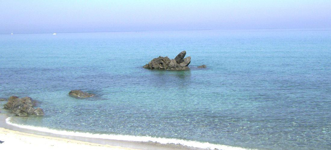 immagine che ritrae una spiaggia e uno scoglio poco lontano